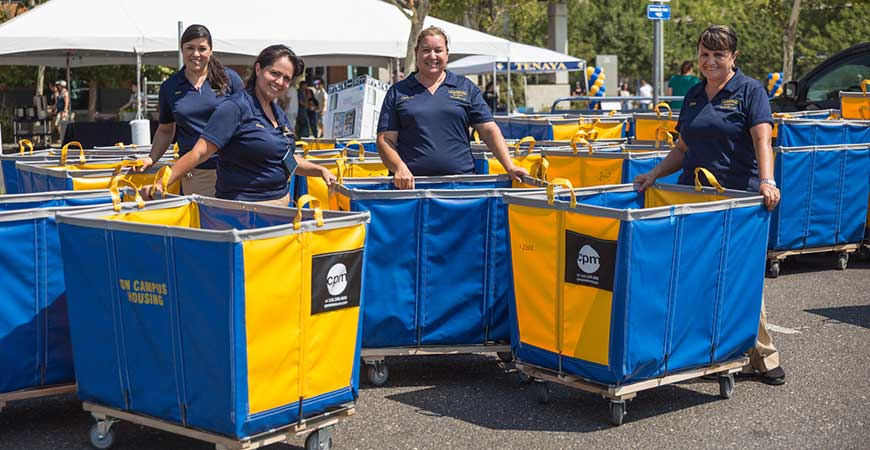Four UC Merced employees pose with blue and gold moving bins.