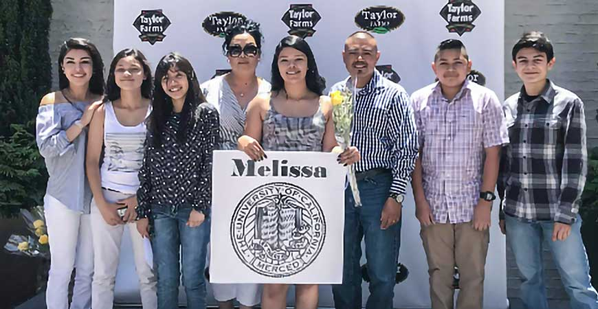 Second-year student Melissa Rios-Arias holds an image of UC Merced's seal while flanked by family members and friends.