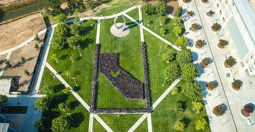 An aerial video of individuals clad in blue formed in the shape of California, with a heart in the middle.