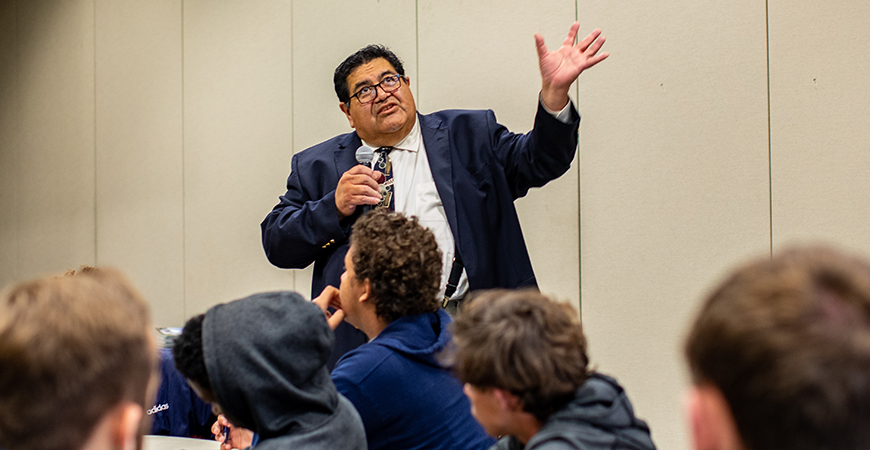 Man in business suits gestures while addressing a crowd of college students
