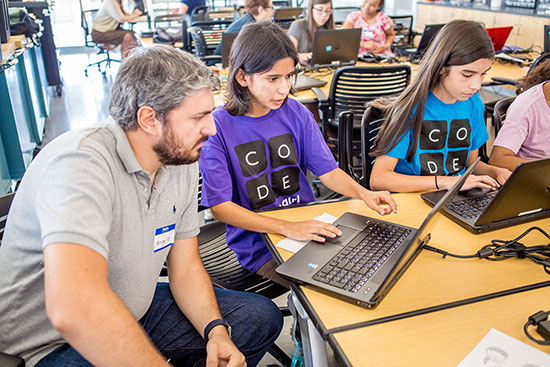 Teaching Professor Angelo Kyrilov works with area high school students on their computer coding skills.
