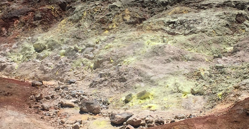 A picture of a soil chronosequence in Hawaii shows yellow sulfur-rich soil that has built up over millions of years.