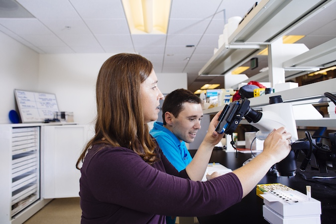 A woman and man sit in front of a microscope in a laboratory.