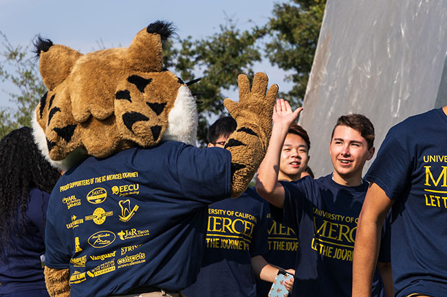 Rear view of a Bobcat mascot high-fiving college students