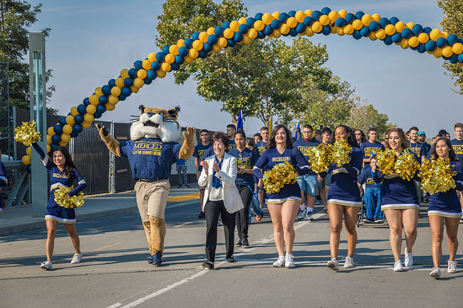 Enthusiastic cheerleaders and bobcat mascot parade under a blue-and-gold balloon arch.