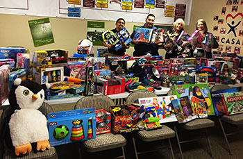 CASA representatives receive gifts donated by UC Merced campus members for children of Merced County.