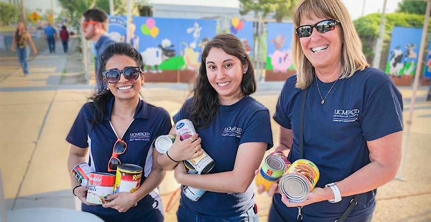 Three women from UC Merced hold canned foods that were donated during a food drive during the Merced County Fair.