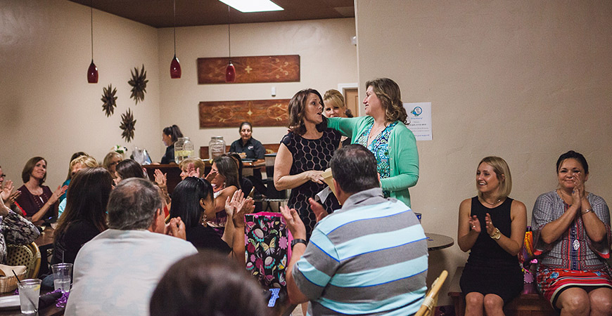 Restaurant crowded with women, two speaking emotionally at a microphone