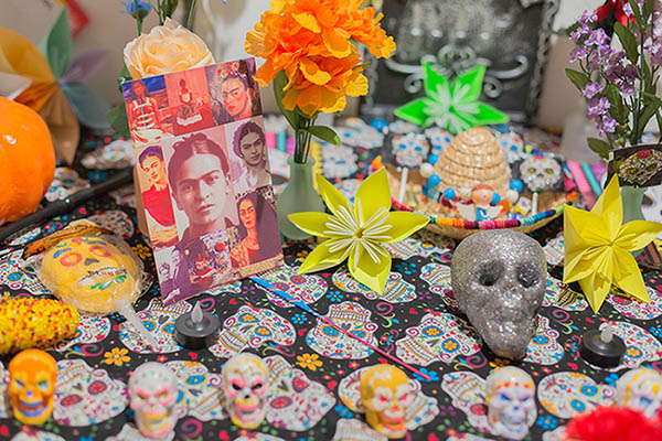 A close up of an altar showcases traditional themes associated with Dia de los Muertos, like skulls and flowers.