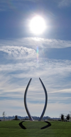 The sun in a cloudy blue sky appears directly above Beginnings sculpture on grassy green landscape.