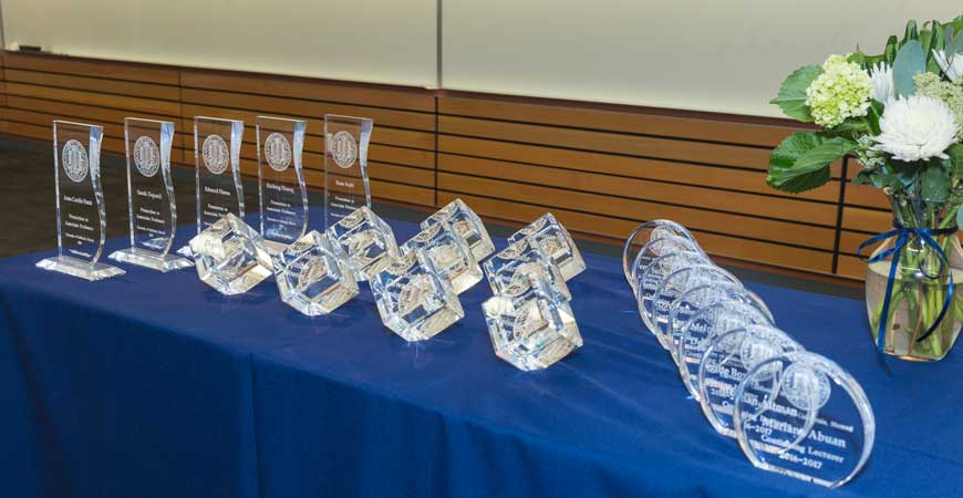 A long table holds a display of crystal awards.