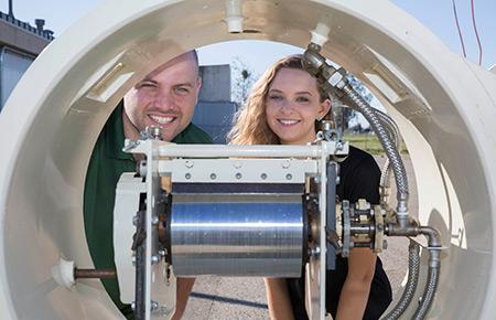 Graduate student Jonathan Ferry and undergraduate mechanical engineering major Jordyn Brinkley show off the solar-powered drum dryer.