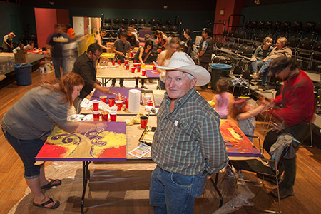 Artist Dwight Wigley stands in front of a group of community members as they paint their portions of an art installation.