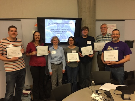 Seven people stand in front of a television screen in a classroom. Six of the seven are holding certificates of commendation noting their participation in the HHMI funded Northstar Summer Institute.