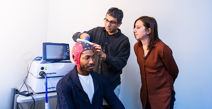 Students and faculty member testing brain-scanning device