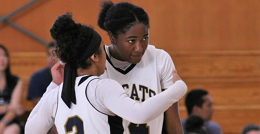 Two UC Merced women's basketball players discuss strategy during a game.