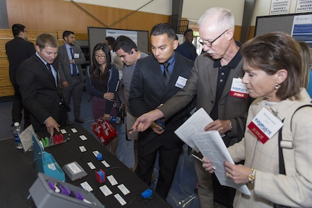 Two competition judges stand in front of a table at the spring 2017 Innovate to Grow as the students explain their projects to the judges.
