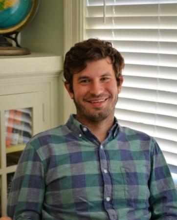 Professor Justin Cook sits in front of a bookshelf and blinds, posing for a photograph.