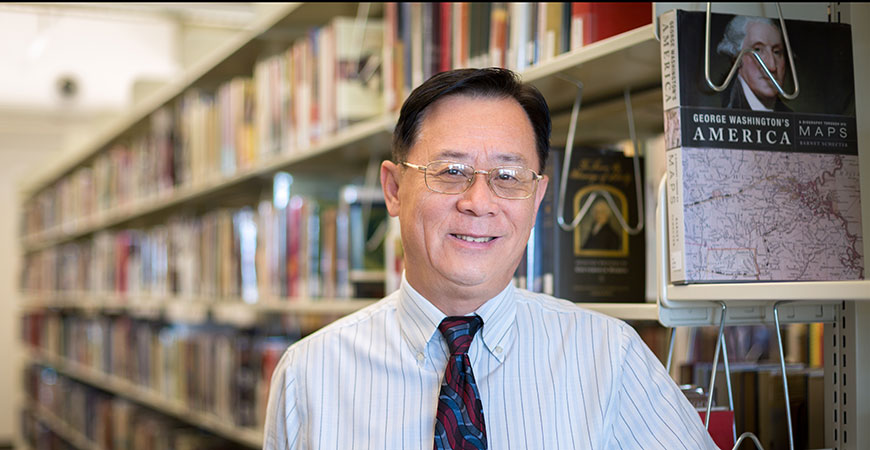 University Librarian Haipeng Li stands next to book shelves in the UC Merced Library