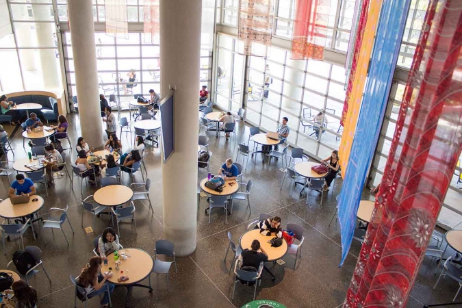 Aerial view of college students studying at round tables in a large space