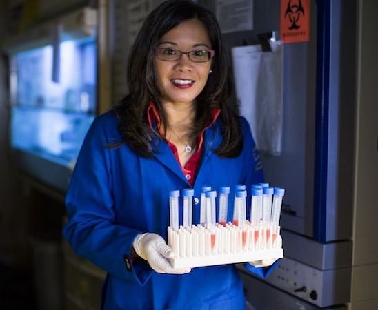 A woman in a blue lab coat holding a rack of test tubes.
