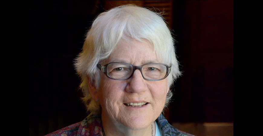 Close-up photo of caucasian woman in glasses with short white hair.