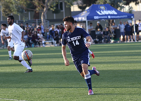 A UC Merced men's soccer player chases after the ball.