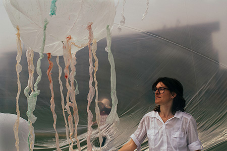 """Artist-in-residence Olga Diego stands inside her """"jellyfish bowl"""" exhibit on the UC Merced campus."""