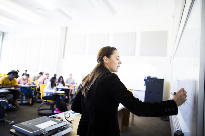 Professor Noemi Petra, pen in hand, writes on a white board in front a classroom full of students.