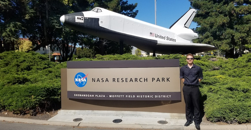 "A student stands in front of a sign that reads ""NASA Research Park."" Above the sign is a model of a NASA space shuttle."