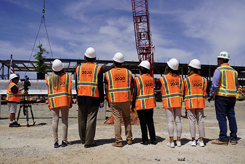 Chancellor Leland and others look on as the final beam of the 2020 Project is raised.