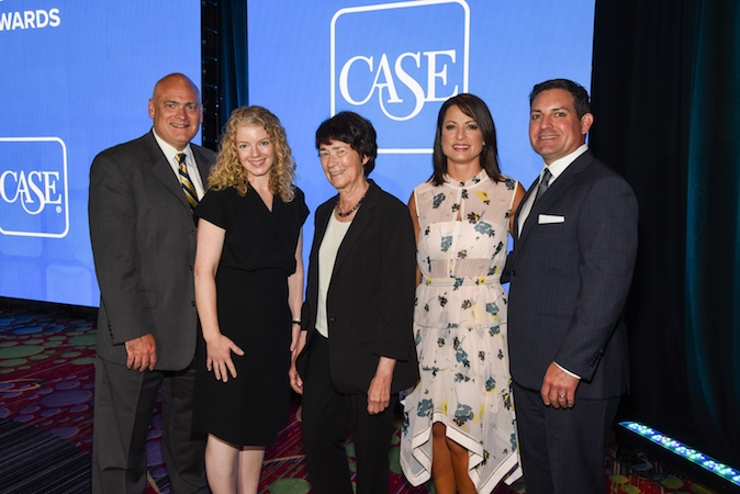 "Two men and three women pose in front a large screen that reads ""CASE"" at the 2018 CASE awards."