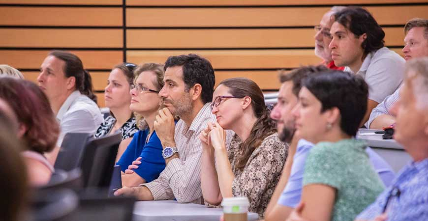 Faculty members listen to a presentation inside a large classroom.