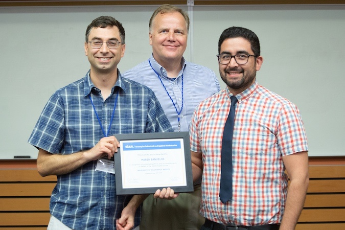 Three men facing the camera pose in front of a whiteboard with one of them holding a certificate.