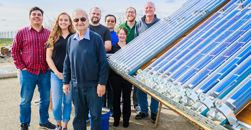 Researchers stand near a large solar collection panel.