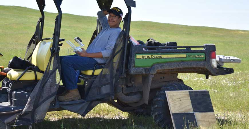 Mechanical engineering major Arturo Ramirez Reyes holds a drone while sitting in a tractor.