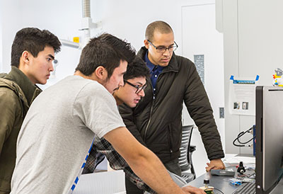Student Success interns Derek Brigham, Jonny Nguyen and Marek Abarca work in Professor Abel Chuang's engineering lab.