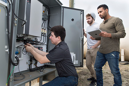 Agustin Roldan, front, Tamba Baldé, center, and Matt Fostiropuls are three of the four members of Sweep Energy,  startup that is working to help area farms monitor their energy use.