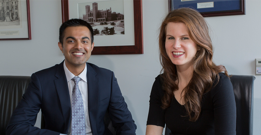 Ehsan Choudhry and Kristen Wanderlich pose seated at a conference table.
