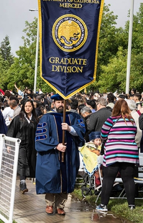 Trevor Albertson ('09), now the dean of Lassen Community College, bears the graduate division flag for the School of Social Sciences, Humanities and Arts at the spring 2019 commencement.