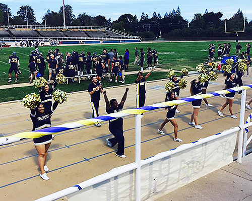 UC Merced's Cheer Team roots for the Merced College Blue Devils' football team.