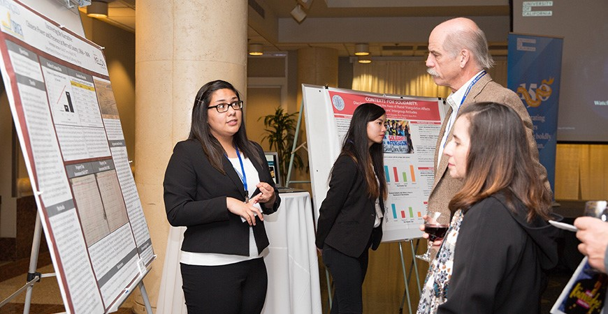 UC Merced's Verenize Arceo presents her research as two onlookers listen.
