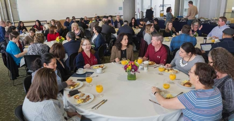 Several dozen UC Merced employees are seated at round tables eating breakfast in Room 355 of Kolligian Library.