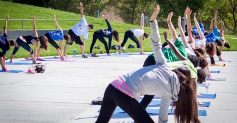 A large group practices yoga outdoors at UC Merced.