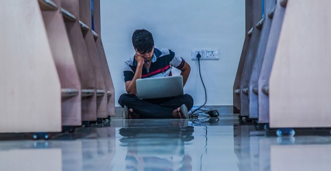 Young man sitting against the wall with head down and laptop computer open on lap